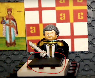 Michael VIII at his study writing on an SD card with the Theodora icon and Byzantine-Genoa flag behind